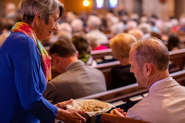 Communion is offered to a worshipper during a service at Bryn Mawr Presbyterian Church