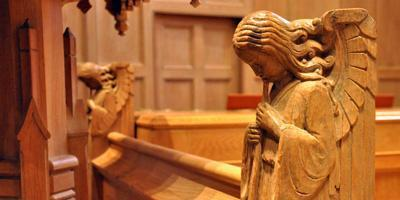 Photo of angel carved in wooden pews in chapel at Bryn Mawr Presbyterian Church
